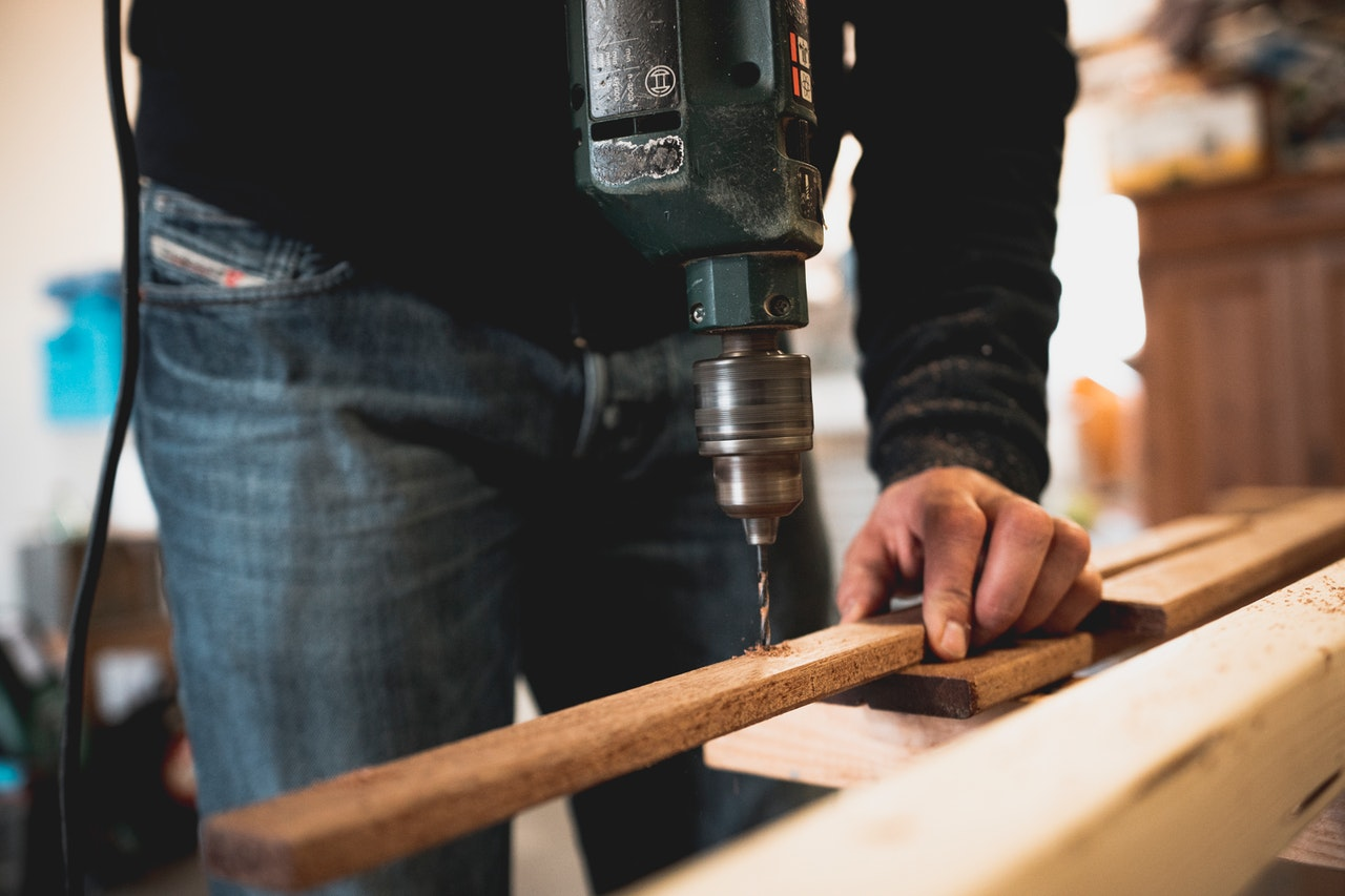 personne qui préparer des plinthes en bois avant de les coller