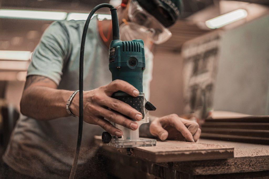 homme qui coupe une planche de bois
